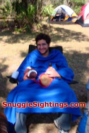 Brian relaxes in his Snuggie, football in one hand, Bota Bag in the other.